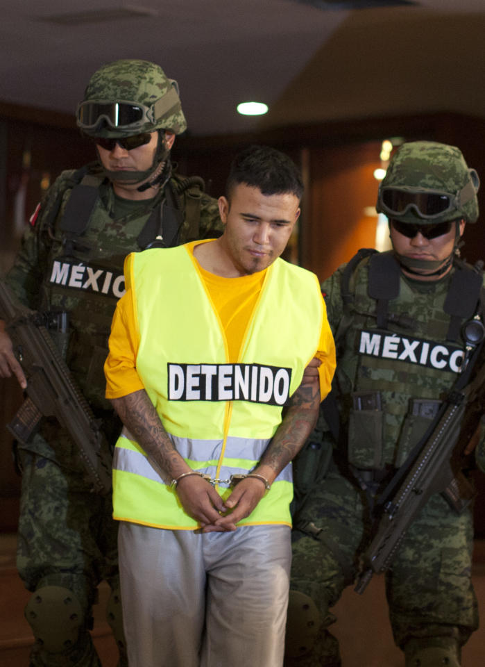 "Army soldiers escort Daniel Ramirez, alias ""El Loco,"" to his media presentation in Mexico City, Monday, May 21, 2012. Ramirez is believed to be a member of the Zetas drug cartel allegedly involved in the dumping of more than 40 hacked-up bodies on a highway outside the city of Cadereyta near Monterrey. The bodies with their heads, hands and feet hacked off were found May 13. (AP Photo/Alexandre Meneghini)"