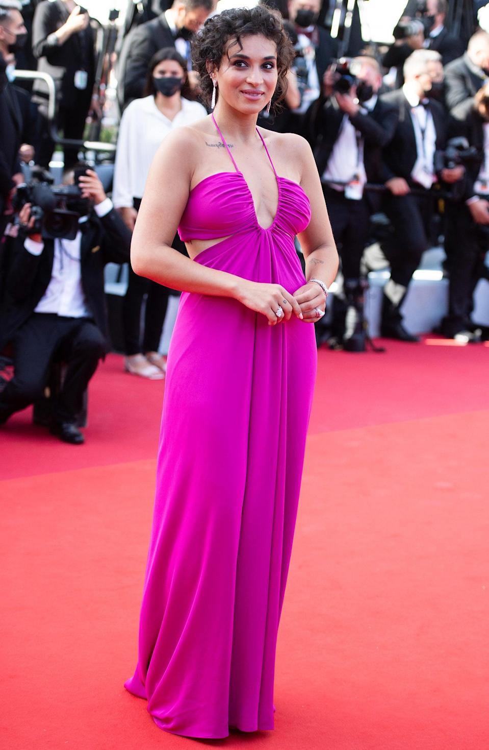 """French singer Camélia Jordana strolled on the red carpet in a magenta halter down with side cut-outs. <br><span class=""""copyright"""">Photo: Samir Hussein/WireImage.</span>"""