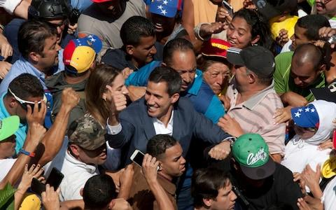 <span>Venezuelan opposition leader Juan Guaido, center, who has declared himself the interim president of Venezuela, greets supporters as he arrives at a nationwide demonstration demanding the resignation of President Nicolas Maduro</span> <span>Credit: AP </span>