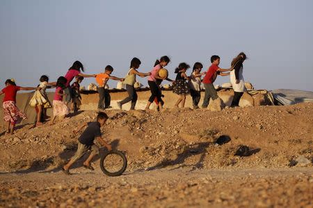 Children, who are internally displaced due to the fighting between rebels and the forces of Syrian President Assad, play inside Al-Tah camp in the southern Idlib countryside