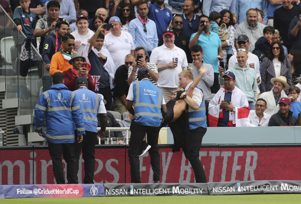 Security officials remove a pitch invader. (AP Photo/Aijaz Rahi)