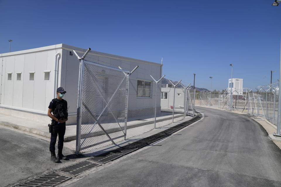 A police officer stands guard at the new closed monitored facility for migrants and refugees in Zervou village, on the eastern Aegean island of Samos, Greece, Friday, Oct. 1, 2021. Greek authorities have moved ten days ago asylum-seekers living in a squalid camp on the island of Samos into a new facility on the island, where access are more strictly controlled. (AP Photo/Thanassis Stavrakis)