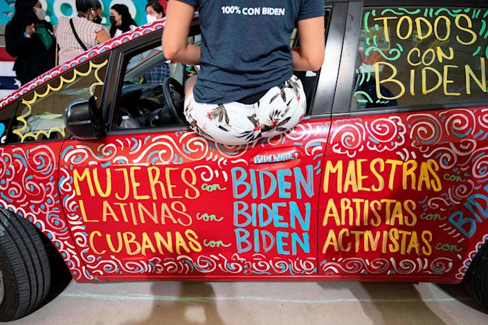 Cuban-American first time voter Sophia Hildalgo leans out the widow of her painted car as Democratic Presidential Candidate Joe Biden speaks during a drive in rally in Miramar, Florida on October 13, 2020.