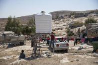 Children play by a new water tank that replaced a damaged one following a settlers' attack from nearby settlement outposts on the Palestinian Bedouin community, in the West Bank village of al-Mufagara, near Hebron, Thursday, Sept. 30, 2021. An Israeli settler attack last week damaged much of the village's fragile infrastructure. (AP Photo/Nasser Nasser)