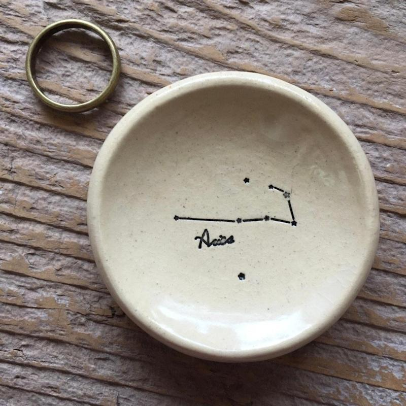 """This pottery ring dish is the perfect personalized gift and it comes in all 12 zodiac signs. <a href=""""https://www.etsy.com/ca/listing/673854264/small-aries-zodiac-constellation-pottery?ref=shop_home_active_2&amp;pro=1"""" target=""""_blank"""" rel=""""noopener noreferrer"""">Get it for $17 on Etsy.</a>"""