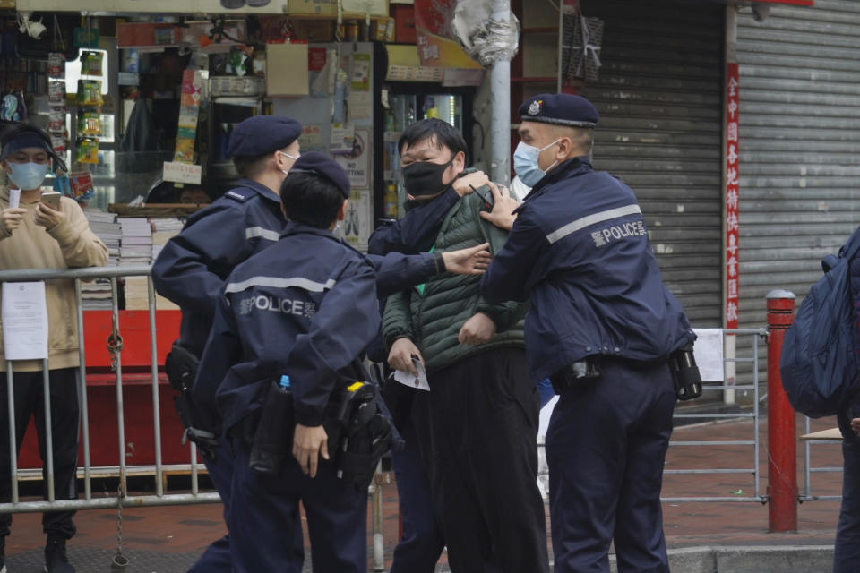 A man is detained after confronting a police officer as he wants to enter the closed area in Jordan area of Hong Kong, Saturday, Jan. 23, 2021. Thousands of Hong Kong residents were locked down Saturday in an unprecedented move to contain a worsening outbreak in the city, authorities said. (AP Photo/Kin Cheung)