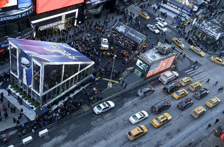 A tent, left, where the Vince Lombardi Trophy is kept during Super Bowl Boulevard festivities, is seen as traffic flows in Times Square Wednesday, Jan. 29, 2014, in New York. The Seattle Seahawks are scheduled to play the Denver Broncos in the NFL Super Bowl XLVIII football game on Sunday, Feb. 2, in East Rutherford, N.J. (AP Photo/Julio Cortez)