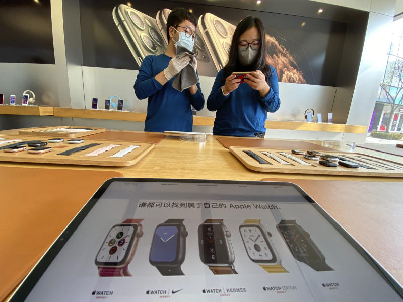 Workers wait for customers at an Apple retail store in Beijing, China on Wednesday, Feb. 19, 2020. U.S. stocks slipped in early trading Tuesday after technology giant Apple became the most well-known company to warn of a financial hit from the virus outbreak in China. (AP Photo/Ng Han Guan)
