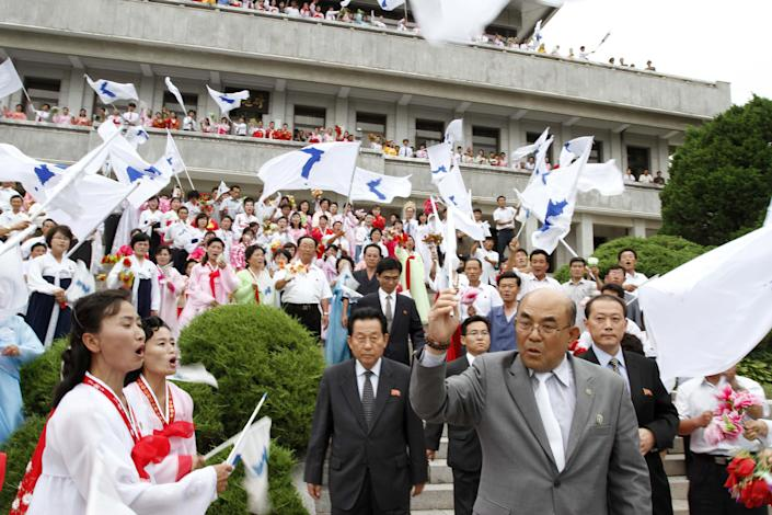 Activist No Su-hui, right, passes North Koreans waving flags depicting a unified Korean peninsula as he walks to the demarcation line between North and South Korea, at the Demilitarized Zone at Panmunjom, Korea, on Thursday, July 5, 2012. No crossed into South Korea and was immediately detained by South Korean officials for making an extended trip to Pyongyang without South Korean government approval as required by law. (AP Photo/Kim Kwang Hyon)