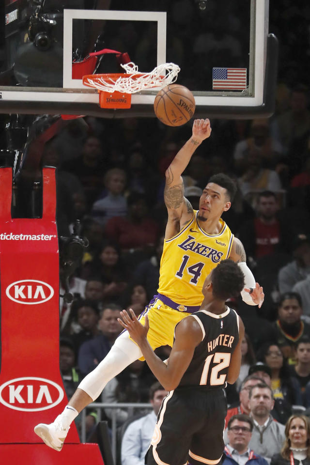 Los Angeles Lakers guard Danny Green (14) scores against Atlanta Hawks forward De'Andre Hunter (12) in the first half of an NBA basketball game Sunday, Dec. 15, 2019, in Atlanta. (AP Photo/John Bazemore)