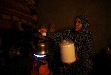 A Palestinian woman makes tea as she uses candle light during power cut in the kitchen of her house in Khan Younis in the southern Gaza Strip July 3, 2017.  REUTERS/Mohammed Salem