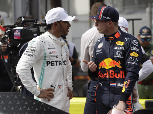 Mercedes driver Lewis Hamilton of Britain, left, who earned pole position, speaks with Red Bull driver Max Verstappen of the Netherland's, who came in the third place, after the qualifying session at the Monaco racetrack, in Monaco, Saturday, May 25, 2019. The Formula one race will be held on Sunday. (AP Photo/Luca Bruno)