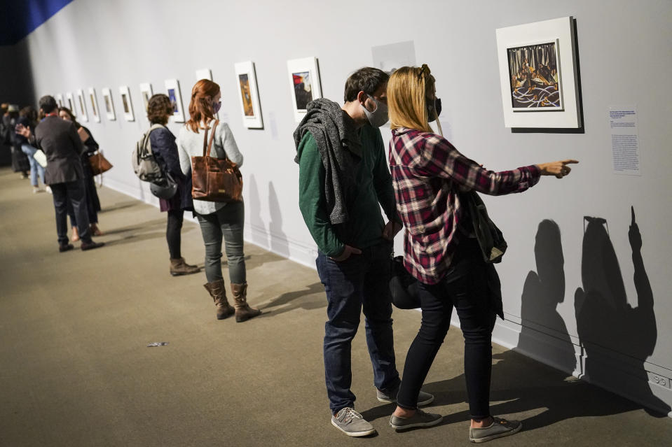 """Visitors wearing protective masks observe COVID-19 prevention protocols as they browse the """"Jacob Lawrence: The American Struggle"""" exhibition at the Metropolitan Museum of Art, Saturday, Oct. 17, 2020, in New York. (AP Photo/John Minchillo)"""