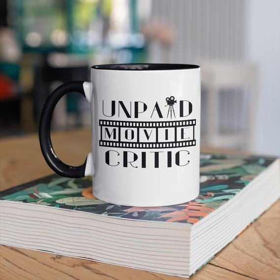"""<p><strong>BeanMugs</strong></p><p>etsy.com</p><p><strong>$14.95</strong></p><p><a href=""""https://go.redirectingat.com?id=74968X1596630&url=https%3A%2F%2Fwww.etsy.com%2Flisting%2F800687529%2Funpaid-movie-critic-mug-cinema-coffee&sref=https%3A%2F%2Fwww.thepioneerwoman.com%2Fholidays-celebrations%2Fgifts%2Fg32417680%2Fgifts-for-movie-lovers%2F"""" rel=""""nofollow noopener"""" target=""""_blank"""" data-ylk=""""slk:Shop Now"""" class=""""link rapid-noclick-resp"""">Shop Now</a></p><p>""""Unpaid movie critic,"""" reads this cheeky coffee mug (which can be used to enjoy a small serving of popcorn!). We like the idea of a cup of coffee and a matinee at home too. </p>"""