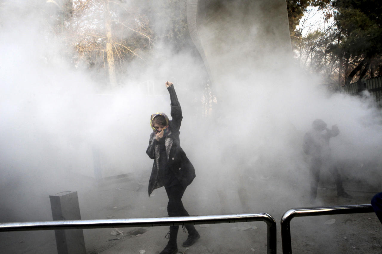 <p>In this photo taken by an individual not employed by the Associated Press and obtained by the AP outside Iran, a university student attends a protest inside Tehran University while a smoke grenade is thrown by anti-riot Iranian police, in Tehran, Iran, Saturday, Dec. 30, 2017. (Photo: AP) </p>