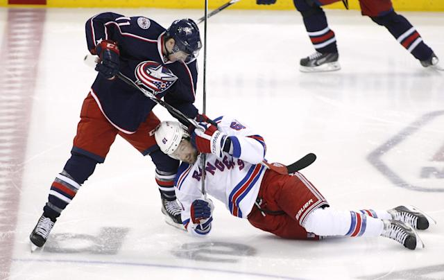 Columbus Blue Jackets' Matt Calvert (11) brings down New York Rangers' Rick Nash (61) at the beginning of the third period of an NHL hockey game, Friday, March 21, 2014, in Columbus, Ohio. A fight ensued after the take down. (AP Photo/Mike Munden)