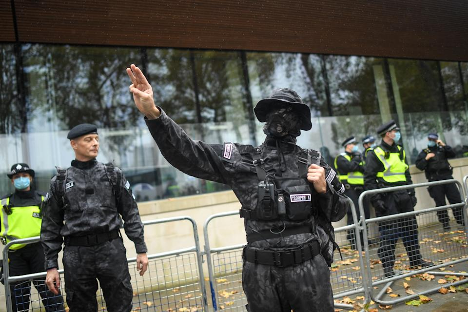 LONDON, ENGLAND - OCTOBER 24: A uniformed man gives a salute during a Unite for Freedom march outside New Scotland Yard on October 24, 2020 in London, England. Hundreds of anti-mask and anti-lockdown protesters marched through central London, England demonstrating against latest Coronavirus lockdown measures. (Photo by Peter Summers/Getty Images)