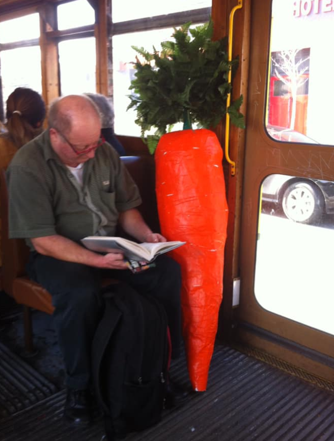 """Nathan """"carrot man"""" on a tram in Melbourne with his giant carrot."""
