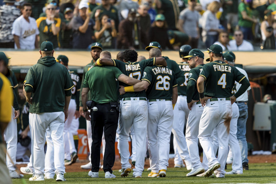 Oakland Athletics teammates help Elvis Andrus, center, off the field after he collapsed with an injury after scoring a walk-off win against the Houston Astros in the ninth inning of a baseball game in Oakland, Calif., Saturday, Sept. 25, 2021. The Athletics won 2-1. (AP Photo/John Hefti)