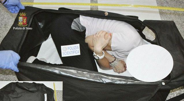 A police officer poses in a suitcase similar to the one the model was allegedly stuffed in after being drugged. Photo: AP