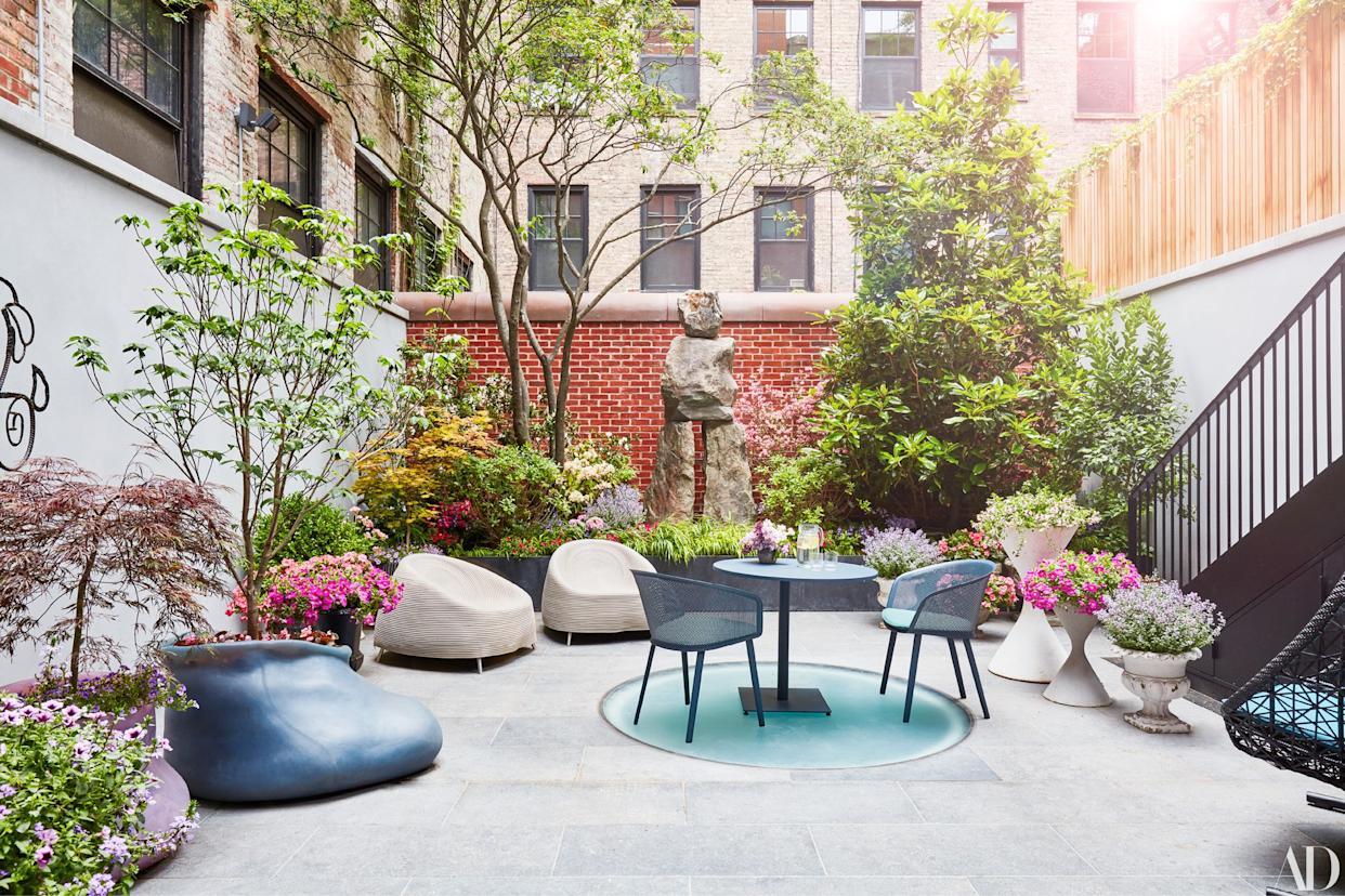 """<div class=""""caption""""> A sculpture by Ugo Rondinone stands in the garden, for which artist Paula Hayes created the custom silicone planter. </div>"""