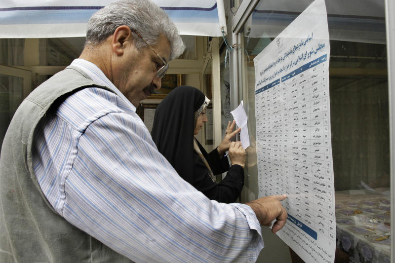 An Iranian couple checks the list of the candidates in the parliamentary runoff elections at a polling station in Tehran, Iran, Friday, May 4, 2012. The country has begun runoff elections for more than one-fifth of parliamentary seats. Friday's report says 130 hopefuls will compete for 65 seats in 33 constituencies including the capital Tehran with 25 undecided seats. (AP Photo/Vahid Salemi)
