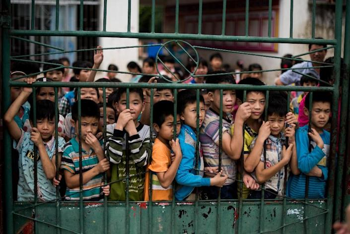 Students gather at the school gates of the Xianghe Primary School, in southern China's Guangxi on June 19, 2015 (AFP Photo/Johannes Eisele)