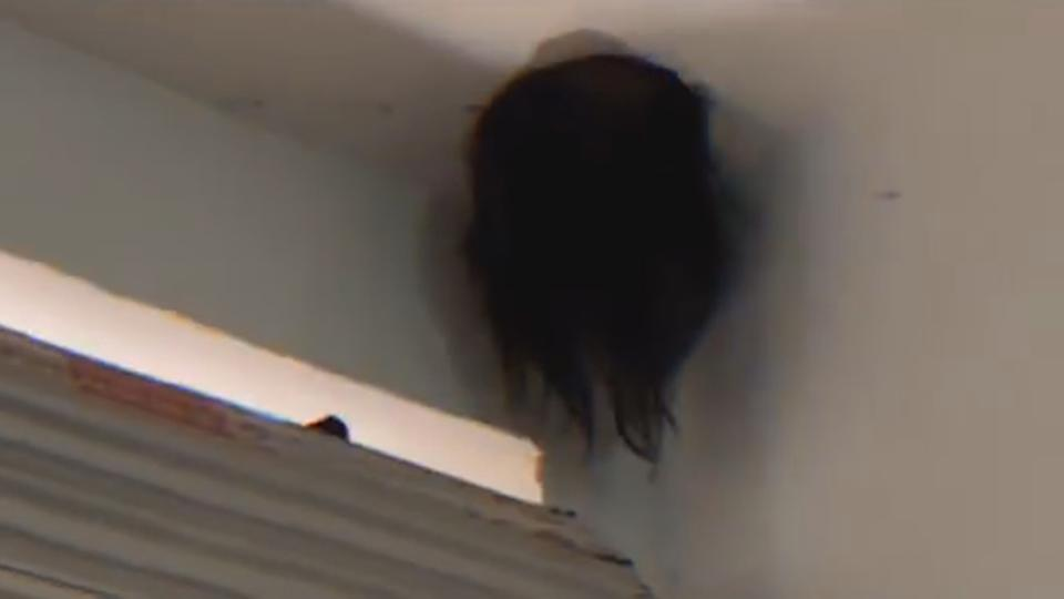 The trapped child's head dangles from the pipe hole in Puding, China.