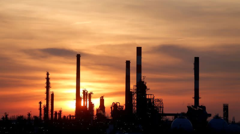 FILE PHOTO: The sun sets behind the chimneys of the Total Grandpuits oil refinery southeast of Paris