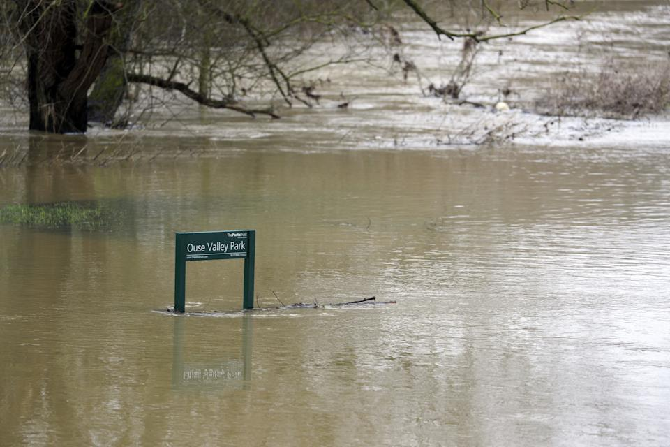 A partially submerged sign post in flooded fields next to the River Great Ouse in Haversham, Buckinghamshire. Heavy snow and freezing rain is set to batter the UK this week, with warnings issued over potential power cuts and travel delays. (Photo by Steve Parsons/PA Images via Getty Images)