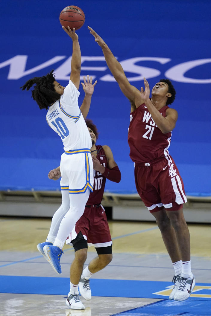 UCLA guard Tyger Campbell (10) shoots against Washington State center Dishon Jackson (21) during the first half of an NCAA college basketball game Thursday, Jan. 14, 2021, in Los Angeles. (AP Photo/Ashley Landis)
