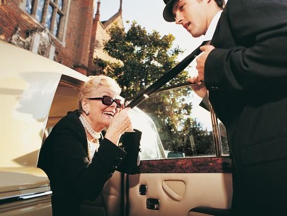 Driver opening car door for older woman in black jacket and pearls
