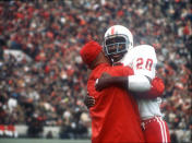 FILE - In this Nov. 25, 1971, file photo, Nebraska's Johnny Rodgers (20) hugs an assistant coach on the sideline after his punt return for a touchdown against Oklahoma in the first quarter of college football game in Norman, Okla., on Thanksgiving Day. The game on Thanksgiving 50 years ago is back in the spotlight as Nebraska and Oklahoma renew their rivalry on Saturday, Sept. 18, 2021. (Lincoln Journal Star via AP, File)