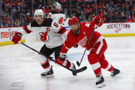 Detroit Red Wings center Luke Glendening (41) and New Jersey Devils defenseman Andy Greene (6) chase the puck during the second period of an NHL hockey game Friday, March 29, 2019, in Detroit. (AP Photo/Paul Sancya)