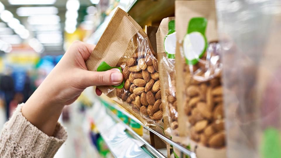 Hand of the buyer with the packaging of almond nuts in the store.
