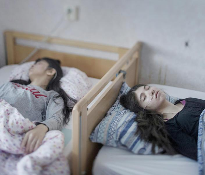 <p>Resignation syndrome: Djeneta (right) has been bedridden and unresponsive for two-and-a-half years, and her sister Ibadeta for more than six months, with uppgivenhetssyndrom (resignation syndrome), in Horndal, Sweden, March 2, 2017.<br>Djeneta and Ibadeta are Roma refugees, from Kosovo. Resignation syndrome (RS) renders patients passive, immobile, mute, unable to eat and drink, incontinent and unresponsive to physical stimulus. It is a condition believed to exist only amongst refugees in Sweden. The causes are unclear, but most professionals agree that trauma is a primary contributor, alongside a reaction to stress and depression. It is also not clear why cases are found exclusively in Sweden. RS has so far affected only refugees aged seven to 19, and mainly those from ex-Soviet countries or the former Yugoslavia. For many, the syndrome is triggered by having a residence application rejected. Granting residence to families of sufferers is often cited as a cure. (Photo: Magnus Wennman/Aftonbladet) </p>