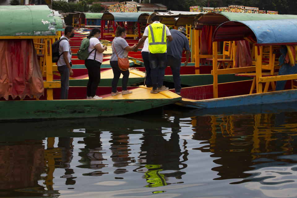 A group board one of the painted wooden boats, known as trajineras, popular with tourists that ply the water canals in the Xochimilco district of Mexico City, after all activities had been on pause for the past six months due to the COVID-19 pandemic. (AP Photo/Marco Ugarte)