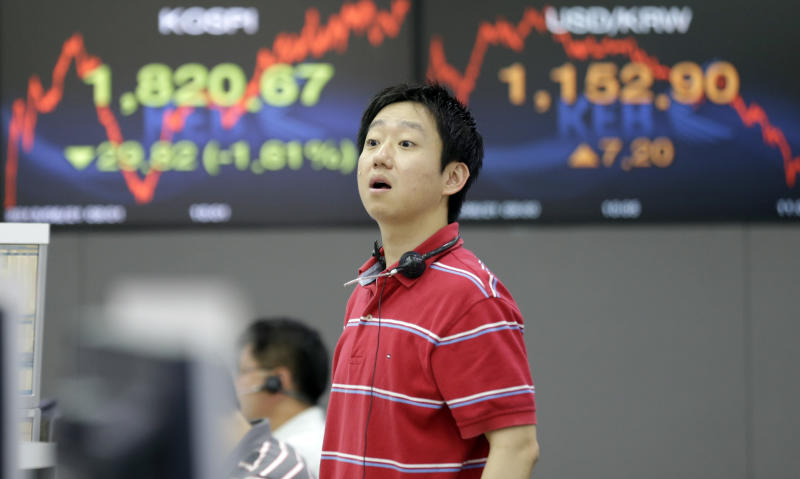 A currency trader asks a question to his colleague near a screen showing the Korea Composite Stock Price Index (KOSPI), left, and foreign exchange rate at the foreign exchange dealing room of the Korea Exchange Bank headquarters in Seoul, South Korea, Friday, June 21, 2013. Asian stock markets took a beating Friday, as a bear market extended amid jitters over U.S. Federal Reserve's plan for early withdrawal of its monetary stimulus program. (AP Photo/Lee Jin-man)