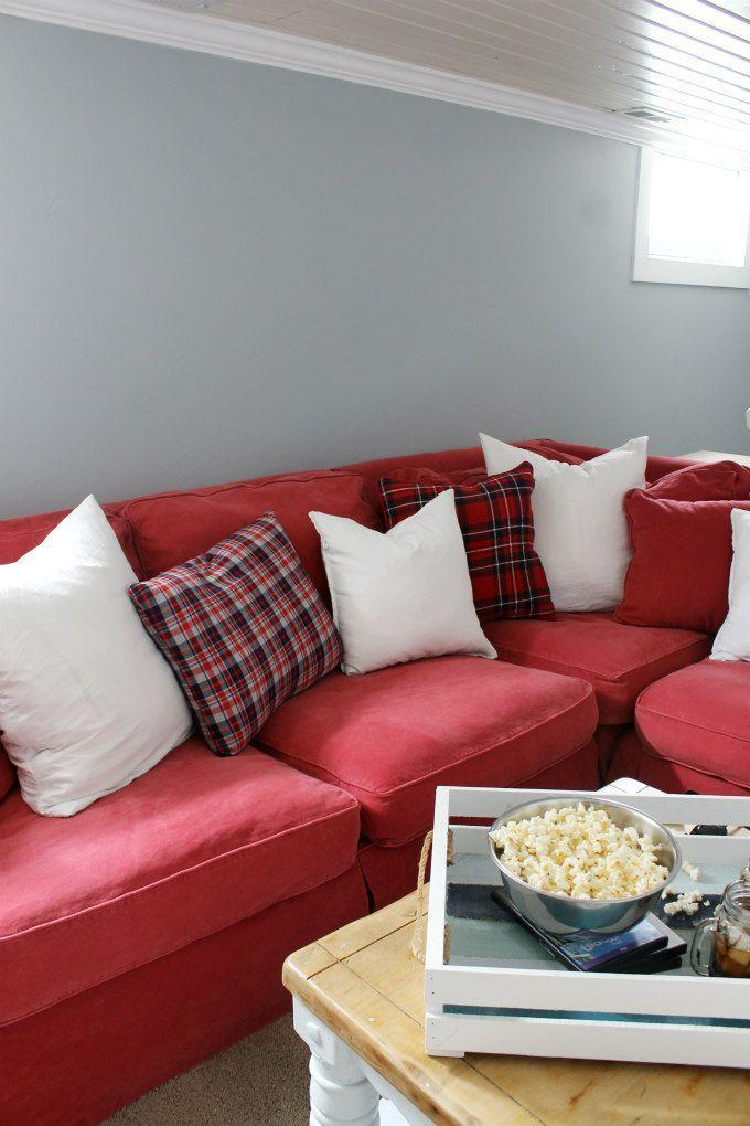 """<p>Give your basement family room a simple holiday refresh with red or green sofa slipcovers and plaid throw pillows. Then get in the Christmas spirit by cuddling up with your loved ones to watch classic Christmas movies. </p><p><strong>See more at <a href=""""https://thewickerhouse.com/2017/02/our-family-roombasement-reveal.html"""" rel=""""nofollow noopener"""" target=""""_blank"""" data-ylk=""""slk:The Wicker House"""" class=""""link rapid-noclick-resp"""">The Wicker House</a>. </strong></p><p><a class=""""link rapid-noclick-resp"""" href=""""https://go.redirectingat.com?id=74968X1596630&url=https%3A%2F%2Fwww.walmart.com%2Fip%2FChristmas-Decorations-Pillow-Covers-Christmas-Buffalo-Plaid-Farmhouse-Decor-Throw-Pillow%2F116779182&sref=https%3A%2F%2Fwww.redbookmag.com%2Fhome%2Fg36061437%2Fbasement-ideas%2F"""" rel=""""nofollow noopener"""" target=""""_blank"""" data-ylk=""""slk:SHOP HOLIDAY PILLOWS"""">SHOP HOLIDAY PILLOWS</a></p>"""