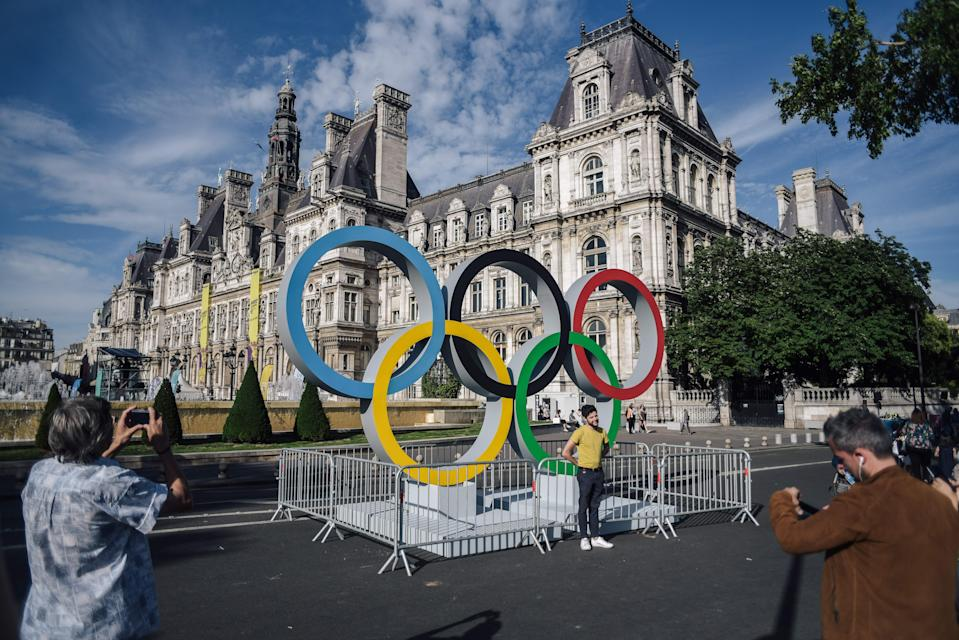"People pose in front of the Olympics rings installed in front of the Paris City Hall during the ""Olympics Day"" organized by the the ""Comite National Olympique et Sportif Francais "" (CNOSF) to celebrate the upcoming of the 2024 Paris Olympics Games, in Paris on June 23, 2018. (Photo by LUCAS BARIOULET / AFP)        (Photo credit should read LUCAS BARIOULET/AFP via Getty Images)"