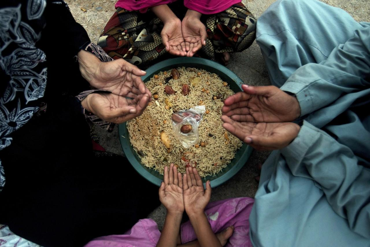 <p>A family pray before breaking their fast during the Islamic month of Ramadan at a free food distribution point in Karachi, Pakistan, Wednesday, June 8, 2016. Muslims across the world are observing the holy fasting month of Ramadan, when they refrain from eating, drinking and smoking from dawn to dusk. (AP/Shakil Adil) </p>