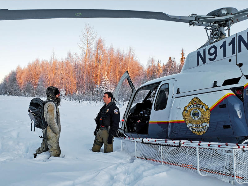 This Jan. 9, 2020 photo provided by Alaska State Troopers shows Tyson Steele, left, talking with Helo 3 Tactical Flight Officer Zac Johnson after Steele's rescue outside Susitna Valley, Alaska. Troopers rescued Tyson Steele, 30, who survived in a makeshift shelter after his remote cabin burned last month, after spotting him and an SOS sign in the snow. (Alaska State Troopers via AP)