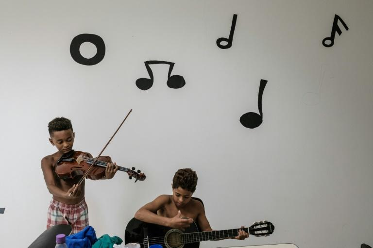 Boys play instruments in a free music class inside a station of the cable car system which is no longer running, over the Alemao favela in Rio de Janeiro, Brazil