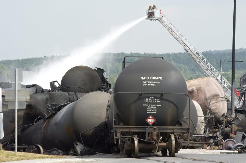 Fire fighters keep watering railway cars the day after a train derailed causing explosions of railway cars carrying crude oil Sunday, July 7, 2013, in Lac Megantic, Que. (AP Photo/The Canadian Press, Paul Chiasson)