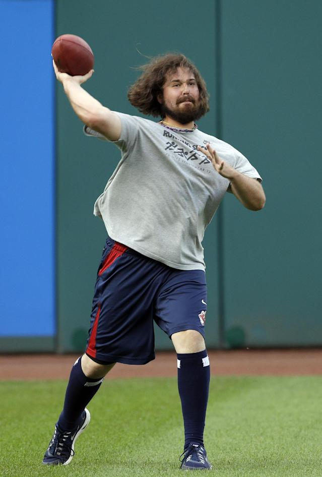 Cleveland Indians relief pitcher Chris Perez throws a football before practice for the American League wild card baseball game Tuesday, Oct. 1, 2013, in Cleveland. The Indians host the Tampa Bay Rays in the AL wild-card game Wednesday night, with the winner advancing to the division series against the Boston Red Sox. (AP Photo/Mark Duncan)
