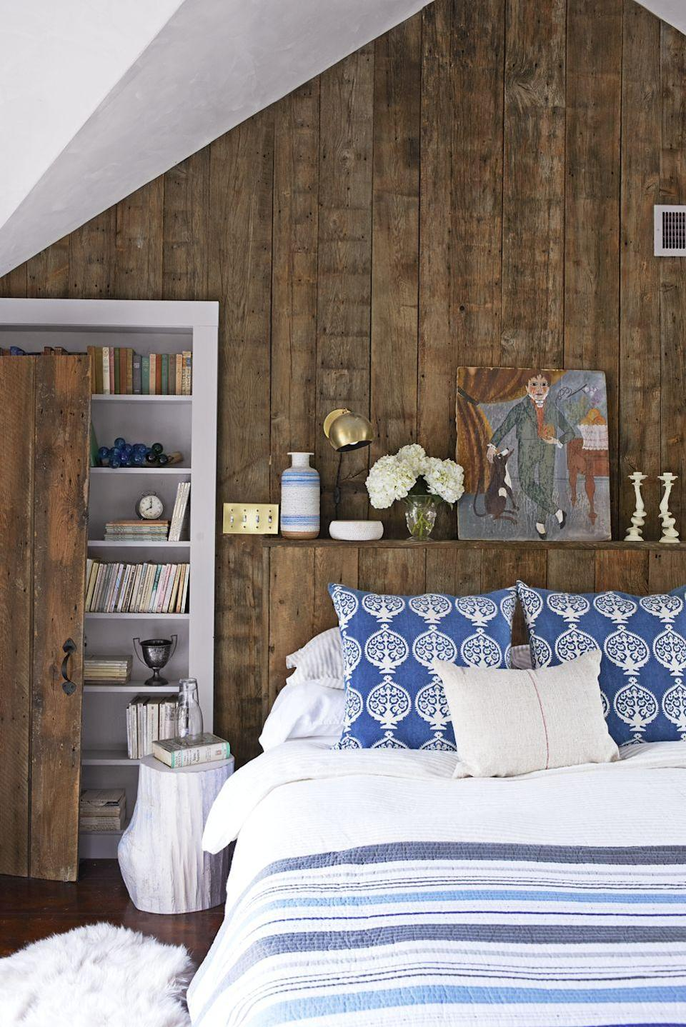 <p>This room gives us major log cabin vibes. A floating shelf above a short headboard shows off artwork, lamps, and other decor, but this bedroom also pulls in an adorable stump-shaped nightstand as an added perch.</p>