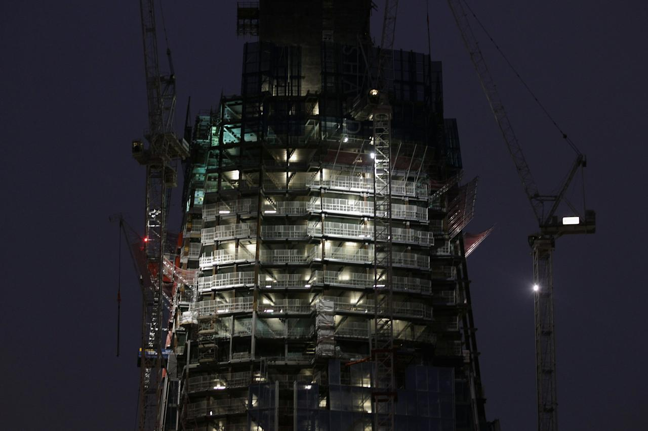 """LONDON, ENGLAND - JANUARY 13:  Work continues on the Shard building on January 13, 2011 in London, England. The Shard, designed by the Italian architect Renzo Piano, will be the tallest skyscraper in the European Union on its completion scheduled for 2012, standing at 1,016 feet (310 metres) and costing an estimated 400 million GBP. The planned 87 storey skyscraper at London Bridge, opposed by English Heritage, was approved back in 2003 by then Deputy PM John Prescott following a public inquiry. Supporters of the project believe the building will be a pivotal moment for the redevelopment of South London but critics remain strongly opposed describing it as a """"spike through the heart of London"""". It will be the 45th tallest building in the world towering over Sir Christopher Wren's masterpiece St Paul's Cathedral and will host a mixture of offices space, hotel apartments, restaurants and a viewing platform.  (Photo by Dan Kitwood/Getty Images)"""