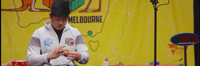 Max Park, a teenager with dark hair, solves a Rubik's cube at a table