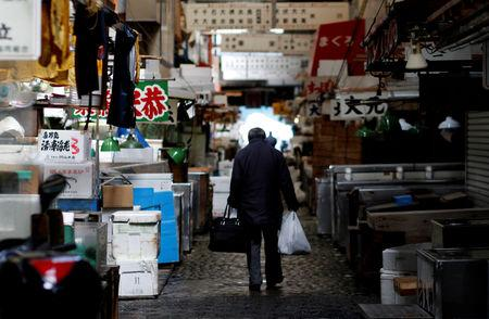 FILE PHOTO - A man walks after shopping at the Tsukiji fish market in Tokyo