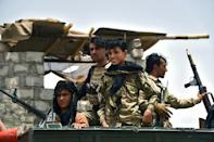 Afghan policemen sit on an armored vehicle at a checkpoint in Panjwai district of Kandahar province on July 4, 2021